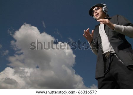 Low-angle view of teenage boy listening to headphones