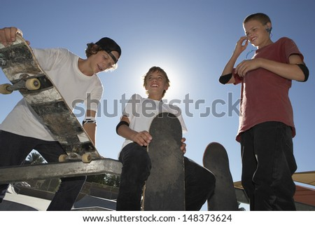 Low angle view of teenage boys with skateboards smiling against blue sky - stock photo