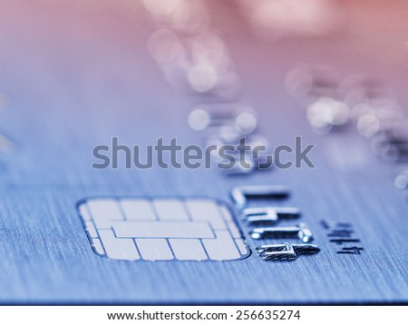 Low angle view of the microchip and raised numbers on a bank card with the expiry date below with shallow dof in a conceptual image - stock photo