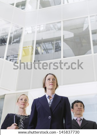 Low angle view of three confidence business people standing in atrium of office building