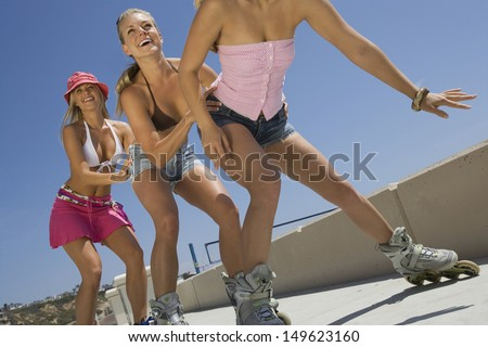 Low angle view of three happy young women on in-line skates - stock photo