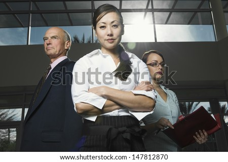 Low angle view of three serious multiethnic businesspeople - stock photo