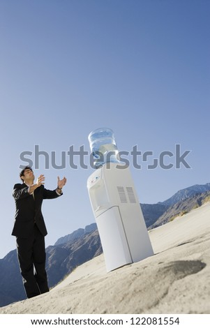 Low angle view of tired businessman looking at water cooler in the desert - stock photo