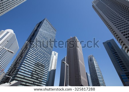 Low angle view of Tokyo skyscraper district with office buildings - stock photo