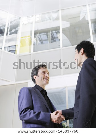 Low angle view of two businessmen shaking hands in office atrium - stock photo