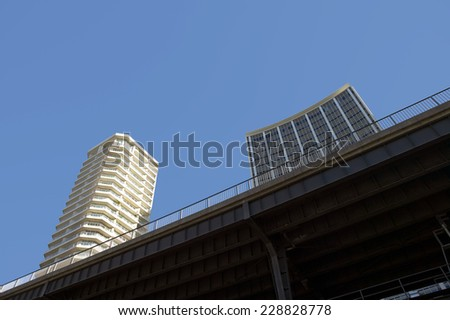 Low angle view of two high-rise buildings behind overpass - stock photo