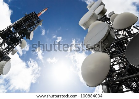 low angle view of two telecommunications towers against the sky - stock photo