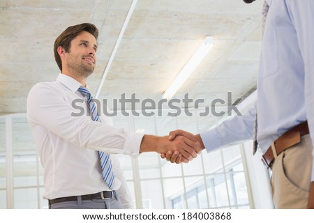 Low angle view of two young businessmen shaking hands in the office - stock photo