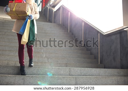 Low angle view of woman with gifts and shopping bags moving down steps - stock photo