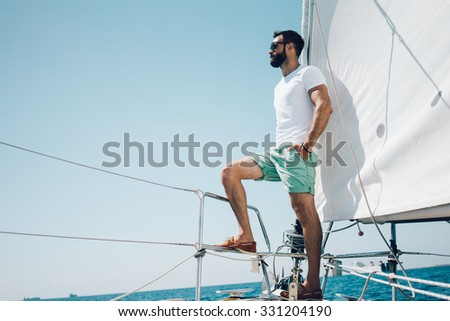Low angle view of young bearded man standing on the nose yacht - stock photo