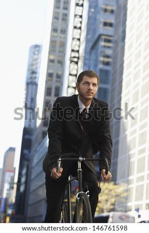 Low angle view of young businessman riding bicycle on urban street - stock photo
