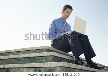 Low angle view of young businessman using laptop while sitting on marble staircase against clear sky - stock photo