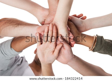 Low angle view of young college students stacking hands against white background