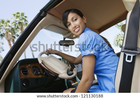 Low angle view of young Indian business woman in car holding steering wheel - stock photo