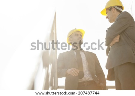 Low angle view of young male architect having discussion on stairway against clear sky - stock photo