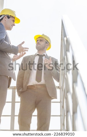 Low angle view of young male businessmen in hard hats having discussion on stairway against clear sky - stock photo