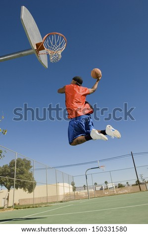 Low angle view of young man dunking basketball into hoop against clear blue sky - stock photo