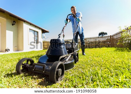 low angle view of young man mowing lawn at home - stock photo