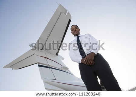 Low angle view of young pilot standing with airplane tail in background - stock photo