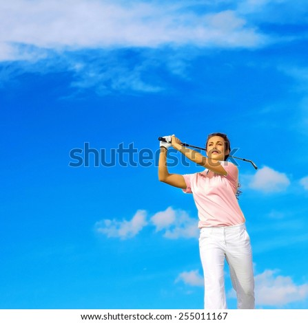 Low angle view of young woman swinging golf club against blue sky