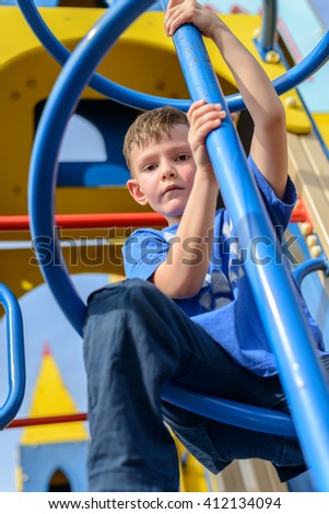 Low angle view on little boy in blue shirt and pants climbing twisted pole on play castle with blue sky behind him - stock photo