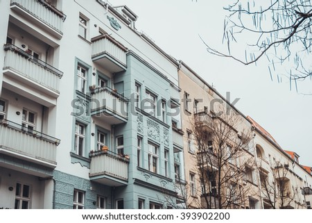 Low angle view on modern white, green and pink apartment building exteriors with bare trees in foreground under overcast sky in Berlin, Germany - stock photo