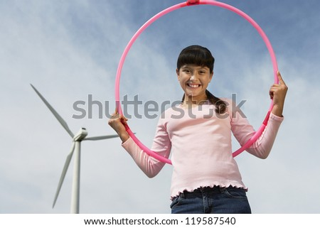 Low angle view portrait of happy teenage girl with hula hoop against wind turbine and cloudy sky - stock photo