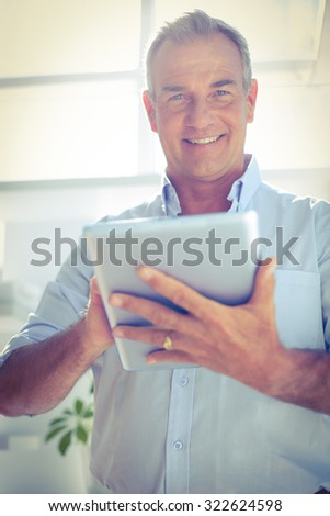 Low angle view portrait of smiling businessman holding digital tablet - stock photo
