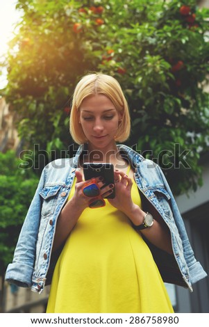 Low angle view with pretty young woman hold smart phone standing on mandarin tree background in city, lost female tourist using telephone for navigation, student girl browsing internet on mobile phone - stock photo