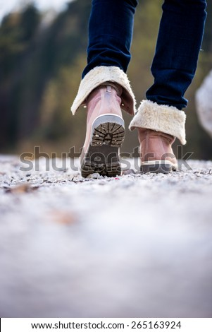 Low angle view with shallow dof of the feet of a woman in jeans and ankle high leather boots walking along a rural path away from the camera. Conceptual of outdoors activity. - stock photo