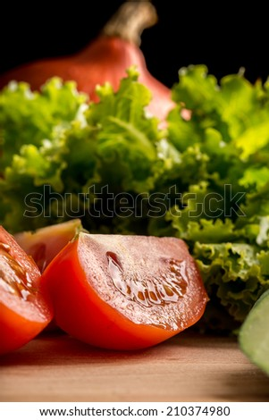 Low angle view with texture of a fresh juicy ripe red sliced tomato on a wooden chopping board with fresh leafy green lettuce for making a healthy salad - stock photo