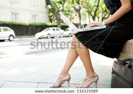 Low body section of a businesswoman using a laptop computer while sitting in a leafy classic city street.