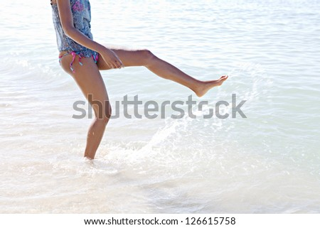 Low body section of a young woman bathing in the sea,  joyfully kicking the waves and splashing water on the shore of a sunny beach while on vacations. - stock photo