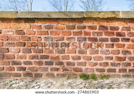 Low brick wall with trees and blue sky behind it