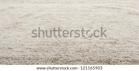 Low close up view of a beige furry carpet texture background, full frame.