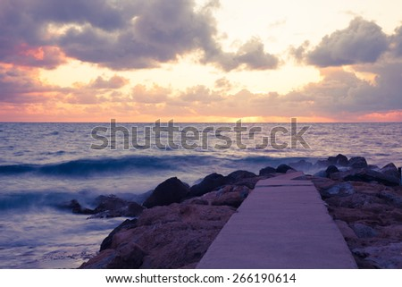Low clouds above the stony shore of the sea and pier. Sunset seascape. Toned. - stock photo