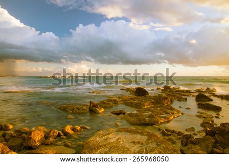 Low clouds above the stony shore of the sea. Seascape. Toned. - stock photo
