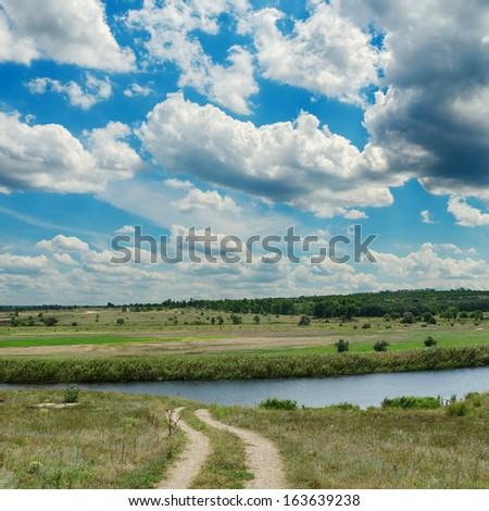 low clouds and dirty road to river - stock photo