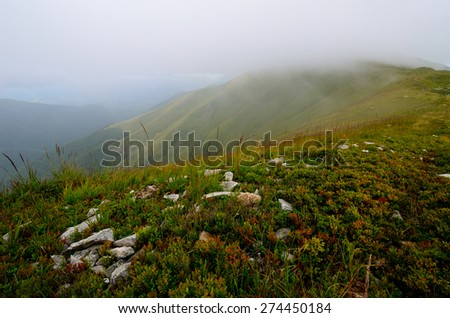 Low clouds near the mountain peak covered with fresh green grass and a lone hiker moving forward - stock photo