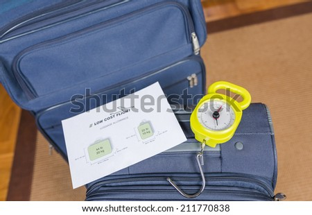 Low cost airlines luggage restrictions and baggage ready to weight with a steelyard balance on the background - stock photo