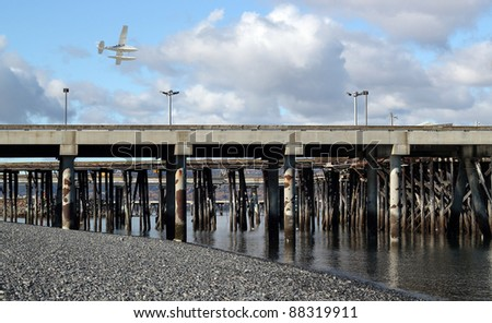 Low flying float plane above the commercial shipping dock in Homer, Alaska on a sunny day with billowing clouds. - stock photo