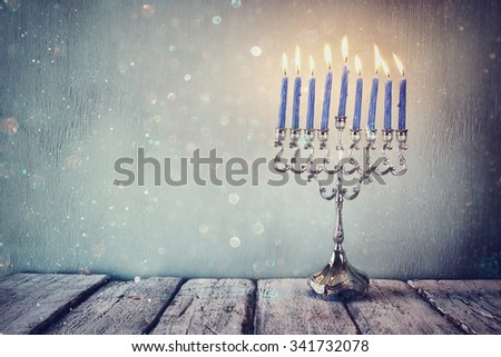 low key and vintage filtered image of jewish holiday Hanukkah with menorah (traditional Candelabra). glitter overlay - stock photo