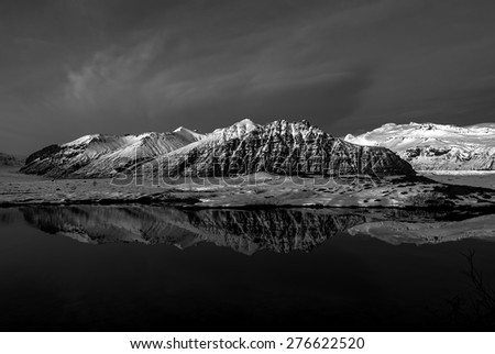 Low key black & white image of the scenic Vatnajokull National Park in the late afternoon, with snow covered mountains and volcanoes, and calm lakes reflecting the blue skies.