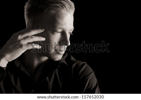 Low-key close up portrait of young attractive man in dark shirt with hand at temple looking aside, black and white, isolated on black background.