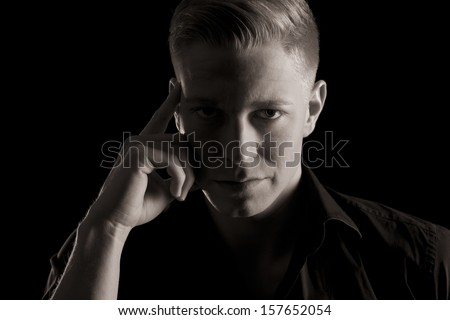Low-key close up portrait of young serious man in dark shirt looking straight, black and white, isolated on black background.