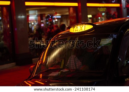 Low key detail of London black cab sign turned on at night, with red shop lights in the background. - stock photo