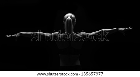 Low key fitness woman on black background.