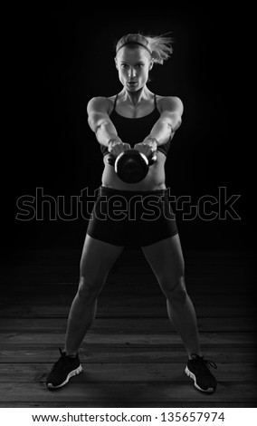 Low key fitness woman working out with kettle bell - stock photo