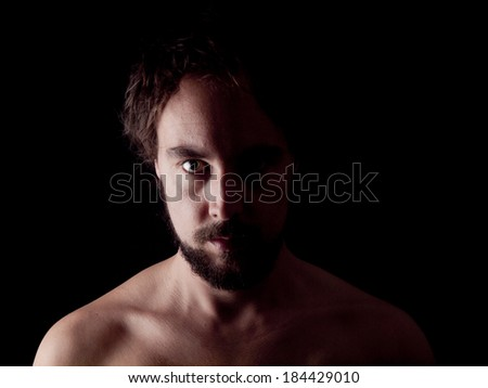 Low key image of a bearded man - stock photo