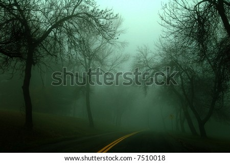 low key image of a country road on a misty and foggy morning - stock photo
